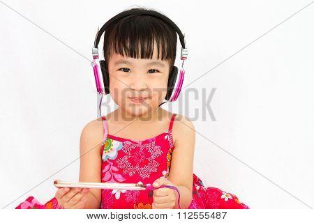 Chinese Little Girl On Headphones Holding Mobile Phone