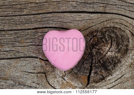Happy Valentines Day With Single Pink Heart Shaped Candy On Rustic Wood
