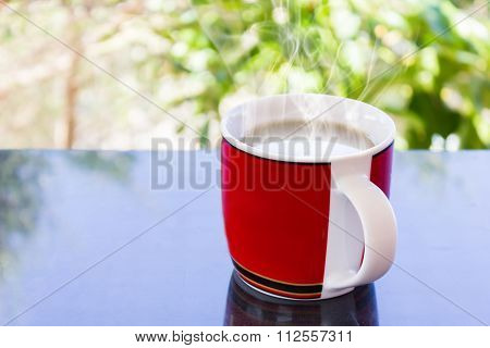 Classic Red Cup Of Black Coffee And Tree Background