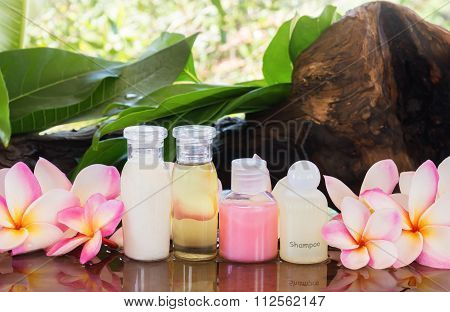 Mini Set Of Bubble Bath And Shower Gel Liquid On Wood Shelf Decorated With Pink Flower