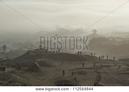 Tourist Trekking Along Mount Bromo Misty Ridge.
