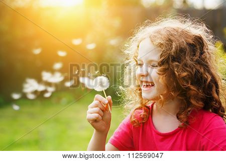 Little Curly Girl Blowing Dandelion And Laughing.
