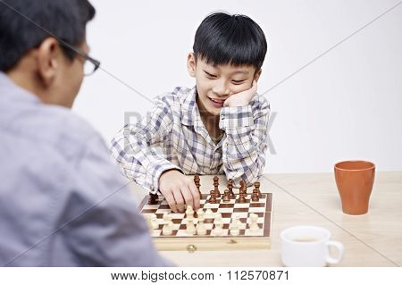 Asian Father And Son Playing Chess