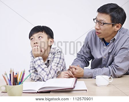 Asian Father And Son Having A Serious Conversation