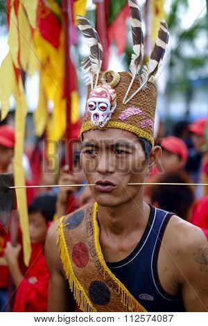 The shaman Sticking steels wire into his cheeks.