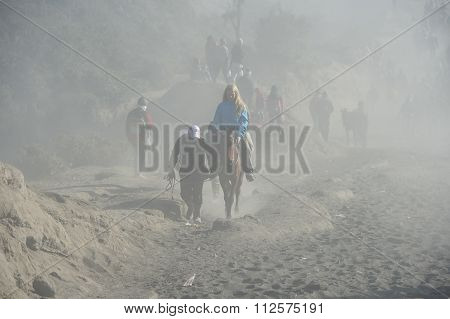 ourist trekking along Mount Bromo misty ridge during sunrise.
