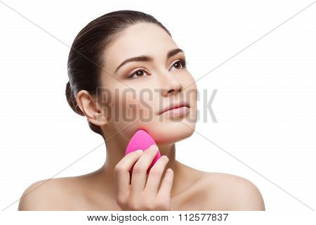 Beautiful girl applying foundation with sponge