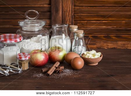 Ingredients And Tools For Baking - Flour, Eggs, Butter, Apples, Cinnamon On A Brown Rustic Wooden Su
