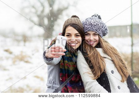 Two teenage girlfriends taking a selfie in winter