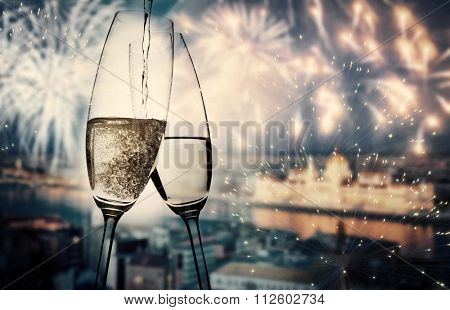 New year in the city - champagne glasses and city lights in the background