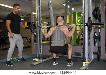 Man With His Personal Fitness Trainer In The Gym Exercising
