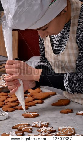 Pastry chef woman preparing christmas cookies holding a vanilla cream cone.