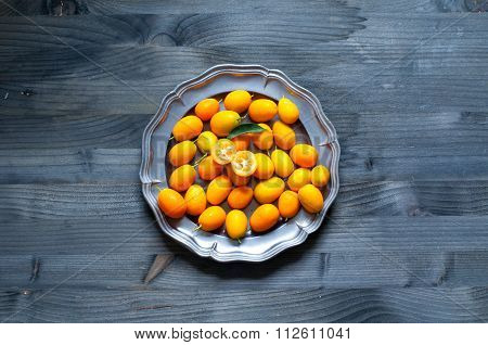 Plate Of Chinese Mandarins On Wooden Background