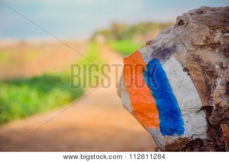 Hiking trail marker (Israel Trail) painted on a stone in countryside area