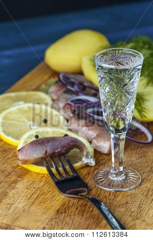 Glass of vodka, fork, herring, potatoes and onion