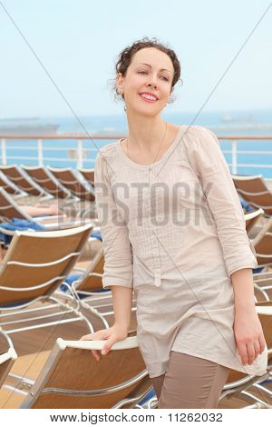 beautiful woman standing on deck of cruise ship