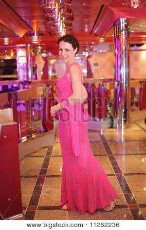 smiling woman wearing evening dress standing in illuminated hall