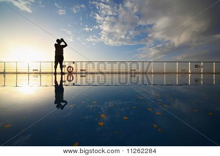 man with compact photo camera shooting morning sky from deck of cruise ship