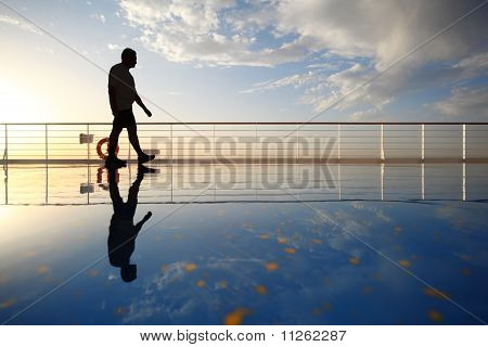 silhouette of old man walking throught deck of cruise ship.