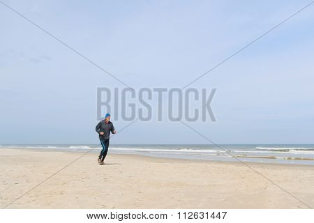 Senior man in black clothes running at the beach