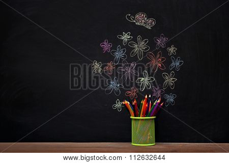 Funny composition of office supplies and pictures drawn with chalk on blackboard