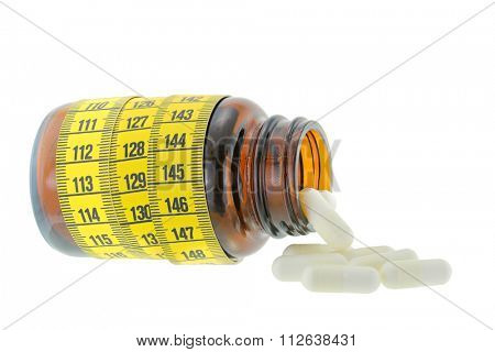 A brown medicine bottle with yellow measuring tape wrapped around and white capsules falling out, isolated on white background
