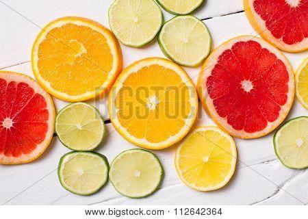 Lemon, tangerine, orange and pink grapefruit on white wood
