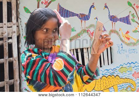 Girl Using Comb And Glass To Straighten Hair At Pingla, West Bengal, India