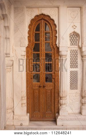 Traditional Narrow Brown Wooden Door With Ornate Stone Doorframe In Junagarh Fort, Bikaner