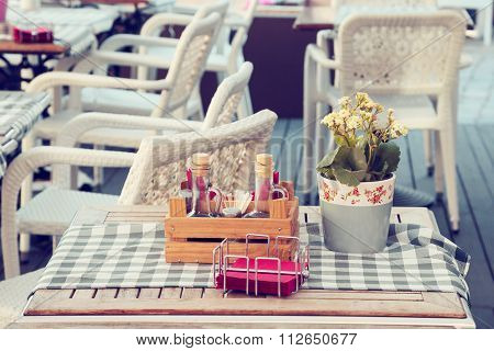 Bottles Of Olive Oil And Vinegar, Flower Pot And Napkins On A Table In Outdoors Cafe.