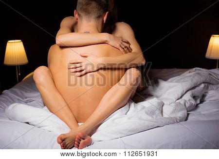 Woman sitting in mans lap and hugging him