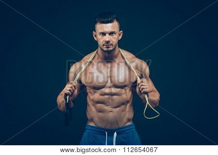 Muscular man skipping rope. Portrait of muscular young men exercising with jumping rope on black bac