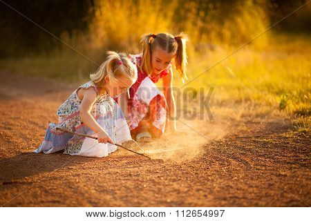Two sisters playing in the dirt at sunset