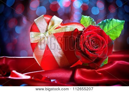 Valentine Red Heart Gift box and Red Rose Flower on Red Silk Background over glowing holiday background. St. Valentine's Day card design. Love