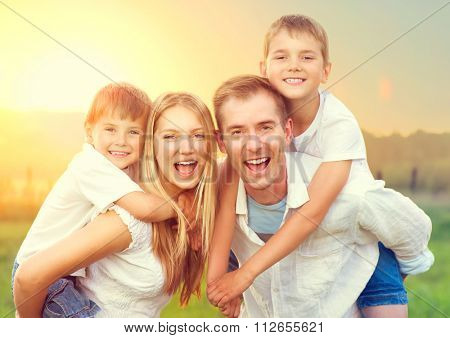 Happy Young Family with two children walking on wheat summer field. Healthy mother, father and little sons enjoying nature together, outdoors. Healthy Smiling Dad, Mom and kids together