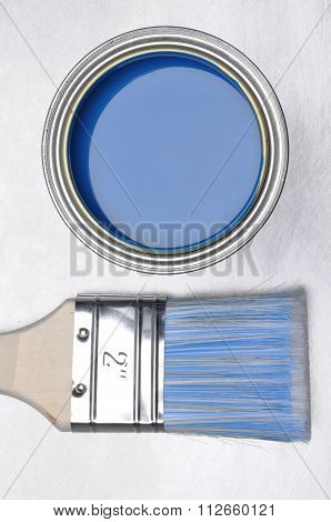 Top view of blue paint can with brush