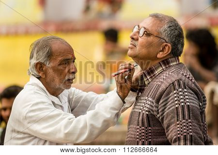 A man being shaved In Varanasi