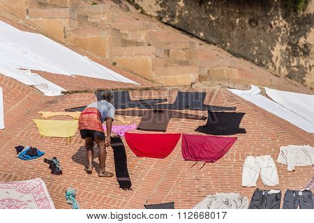 A man laying clothes to dry in sunlight at Varanasi, India.