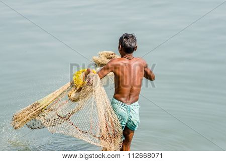 A man fishing with a net in Varanasi, India