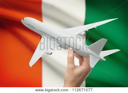 Airplane In Hand With Flag On Background - Ivory Coast
