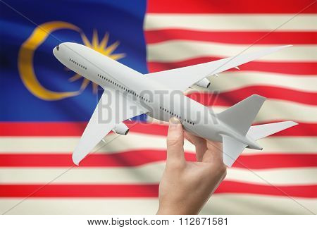 Airplane In Hand With Flag On Background - Malaysia