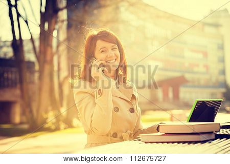 Smiling young woman student talking on mobile phone using tablet in campus university