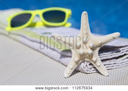 Sea star, towel and sunglasses on sunbed