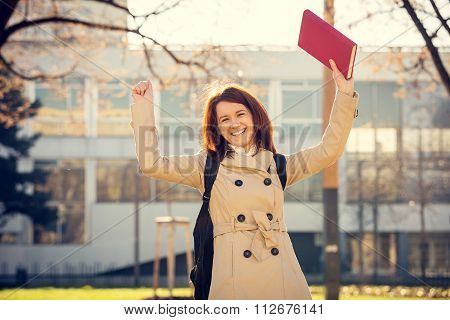 University.Smiling young student girl holding a book on a university background