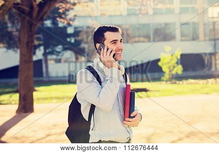 University.Smiling young student mantalking on phone mobile holding a book and a bag on a university