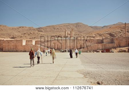 Tourists Walking To Ruined Persepolis City. Unesco World Heritage Site