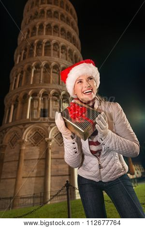 Woman Shaking Christmas Gift Box Near Leaning Tower Of Pisa