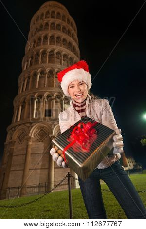 Woman In Santa Hat Giving Gift Box Near Leaning Tower Of Pisa