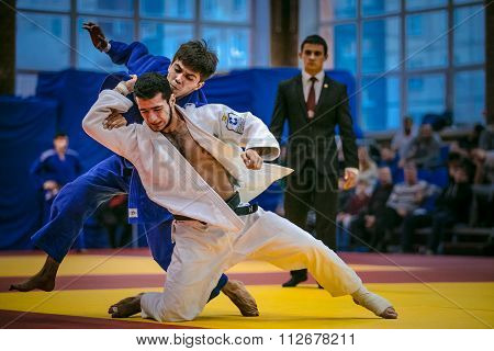fight between young male judoists. in background referee