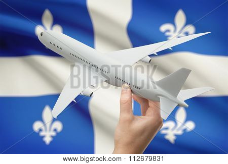 Airplane In Hand With Canadian Province Flag On Background - Quebec